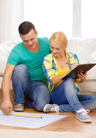 moving, home and couple concept - smiling couple relaxing on sofa and looking at blueprint in new home photo