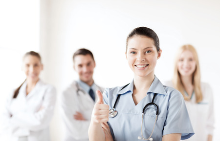 healthcare and medical concept - female doctor with group of medics showing thumbs up photo