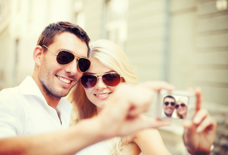 summer holidays and dating concept - couple taking photo in cafe in the city photo