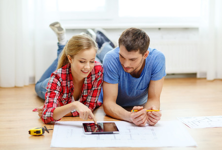 2 people at home: repair, building, renovation and home concept - smiling couple looking at tablet pc at home