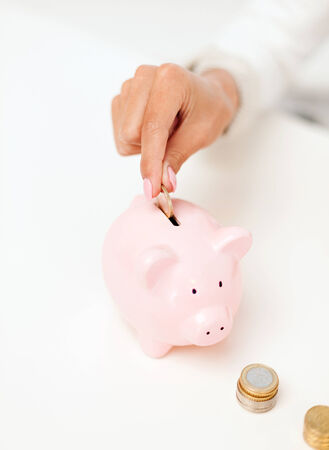 putting in: business and money saving concept - close up of female hand putting euro coins into piggy bank in office