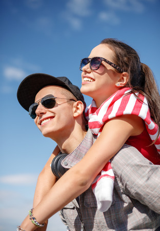 summer holidays, relationships and teenage concept - smiling teenagers in sunglasses having fun outside photo