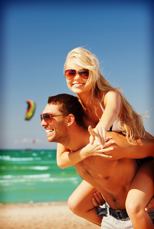 picture of happy couple in sunglasses on the beach  (focus on woman) photo