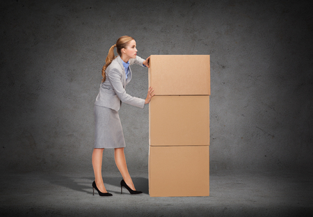 moving office: business, post and transportation concept - busy businesswoman pushing tower of cardboards Stock Photo