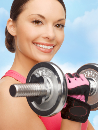 sport, fitness and healthcare concept - beautiful asian sporty woman with heavy dumbbell photo