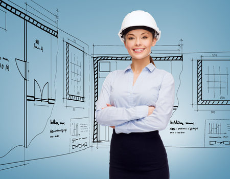 woman engineer: building, developing, consrtuction and architecture concept - friendly young smiling businesswoman in white helmet