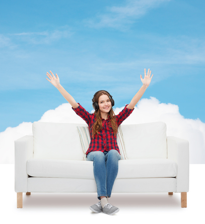 home, leisure and happiness concept - smiling teenage girl sitting on sofa with headphones photo