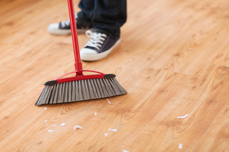 cleaning and home concept - close up of male brooming wooden floor 版權商用圖片