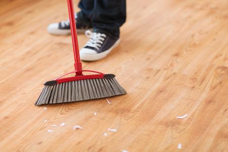 la limpieza y el concepto de hogar - cerca de piso de madera masculina barriendo Foto de archivo