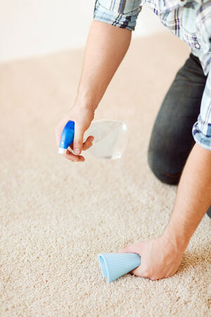cleaning and home concept - close up of male cleaning stain on carpet with cloth photo