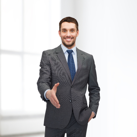 business and office concept - handsome businessman with open hand ready for handshake photo