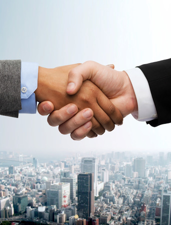 doing business: business and office concept - businessman and businesswoman shaking hands