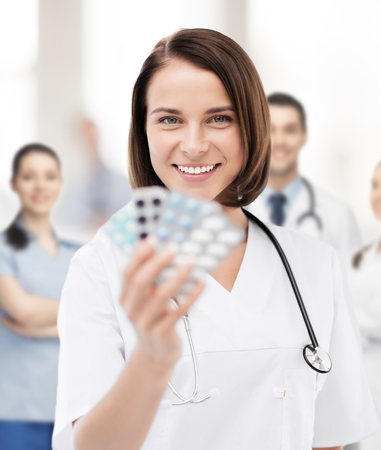 healthcare and medical concept - doctor with blister packs of pills Фото со стока