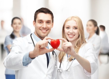 healthcare and medical concept - cardiologists with heart photo