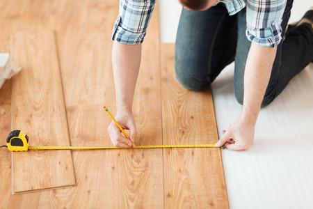 reparatie, bouw en huis concept - close-up van mannelijke handen meten van houten vloeren Stockfoto