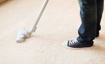 cleaning and home concept - close up of male hoovering carpet photo