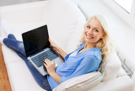home, technology and internet concept - smiling woman sitting on the couch with laptop computer with blank black screen at home