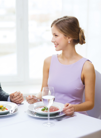 restaurant, couple and holiday concept - smiling young woman looking at husband or boyfriend while eating first course at restaurant photo