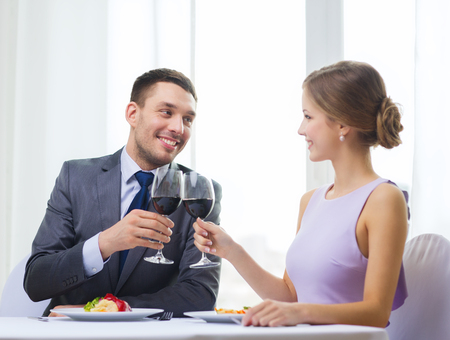 restaurant, couple and holiday concept - smiling couple with main course and red wine at restaurant photo