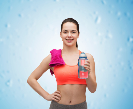 athletic wear: sport, exercise and healthcare - sporty woman with pink towel and water bottle Stock Photo
