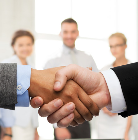 business and office concept - businessman and businesswoman shaking hands photo