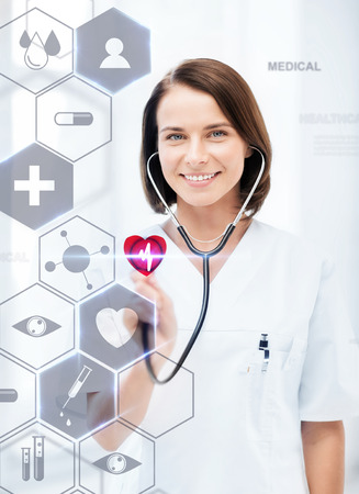 cardiologist: healthcare, medical and future technology concept - female doctor with stethoscope and virtual screen Stock Photo