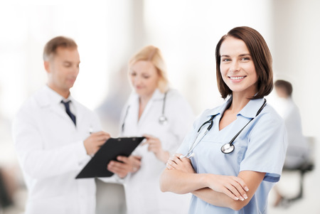 cardiologist: healthcare and medical concept - young female doctor with colleagues in hospital