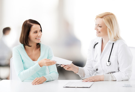 healthcare and medical concept - doctor giving prescription to patient in hospital photo