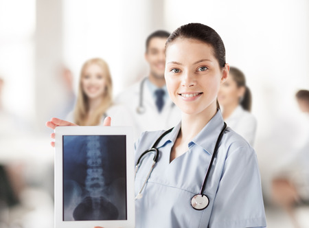 radiology: healthcare, medical and technology concept - female doctor with x-ray on tablet pc Stock Photo