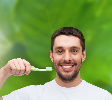 health and beauty concept - smiling young man with toothbrush photo