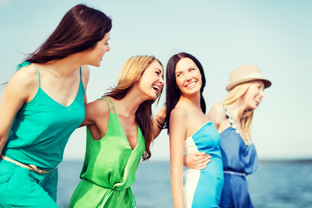 women friends: summer holidays and vacation - girls walking on the beach Stock Photo