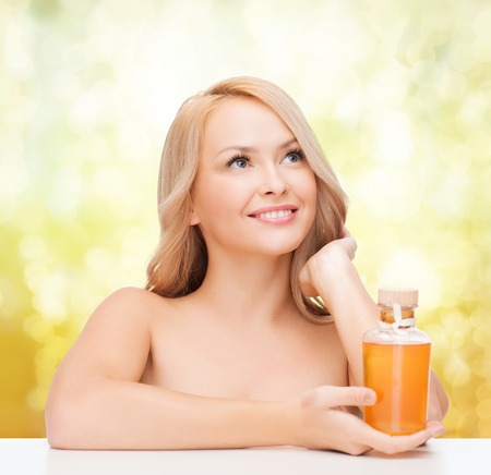 health and beauty concept - happy woman with oil bottle photo