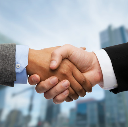 international business agreement: business and office concept - businessman and businesswoman shaking hands