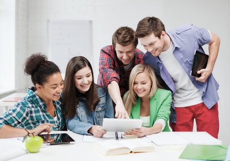 education concept: education concept - smiling students looking at tablet pc at school Stock Photo