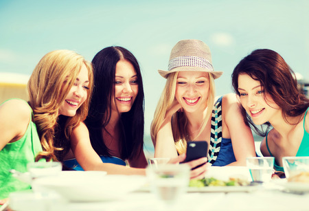 girls friends: summer holidays, vacation and technology - girls looking at smartphone in cafe on the beach