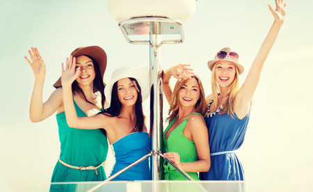 summer holidays and vacation concept - girls waving on boat or yacht photo