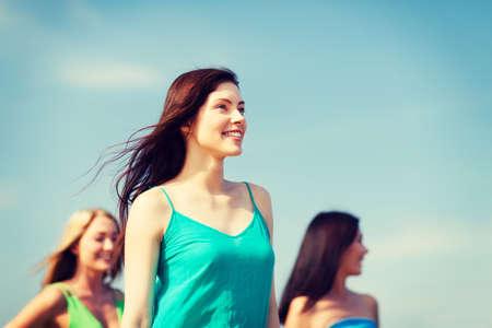 despedida de soltera: vacaciones de verano y vacaciones - niña con amigos caminando en la playa Foto de archivo