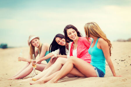 summer holidays and vacation - girls with drinks on the beach photo