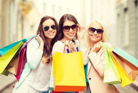 chicas compras: compra, venta, gente feliz y el concepto del turismo - tres hermosas chicas en gafas de sol con bolsas de la compra en ctiy
