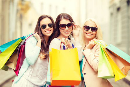 holiday spending: shopping, sale, happy people and tourism concept - three beautiful girls in sunglasses with shopping bags in ctiy