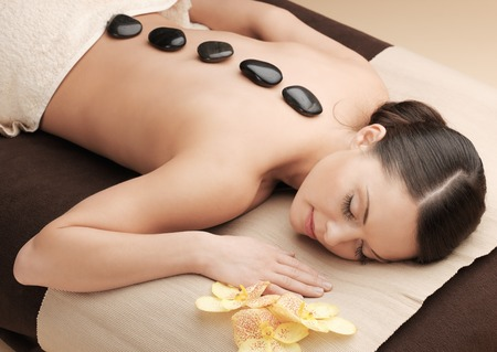 health and beauty, resort and relaxation concept - asian woman in spa salon getting massage with hot stones Stock Photo