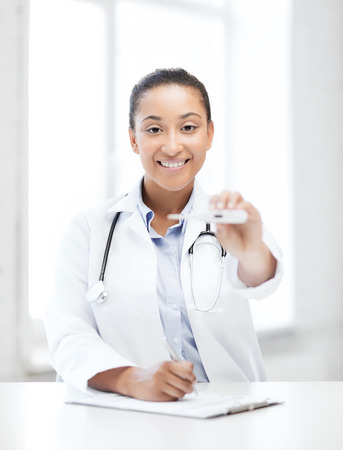 healthcare and medical - female doctor with thermometer and stethoscope photo