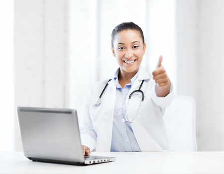 healthcare, medical and technology concept - african female doctor with laptop pc photo