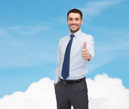 business and office concept - handsome businessman showing thumbs up photo