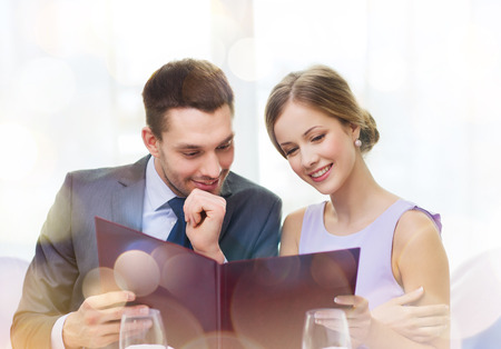 restaurant, couple and holiday concept - smiling couple with menu at restaurant Stock Photo