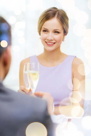 restaurant, couple and holiday concept - smiling woman with glass of champagne looking at husband or boyfriend at restaurant photo