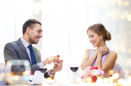 restaurant, couple and holiday concept - smiling man proposing to his girlfriend at restaurant Stock Photo