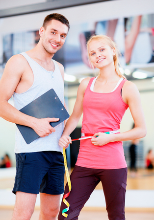 fitness, sport, training, diet, gym and lifestyle concept - two smiling people with clipboard and measure tape in the gym photo