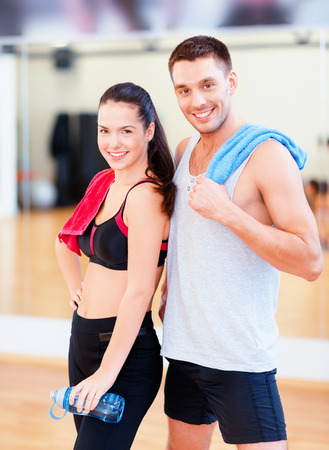 man working out: fitness, sport, training, gym and lifestyle concept - two smiling people in the gym
