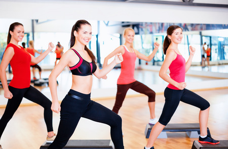 fitness, sport, training, gym and lifestyle concept - group of smiling people doing aerobic photo